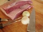 Fleisch in passende Stücke schneiden und Zwiebel halbieren